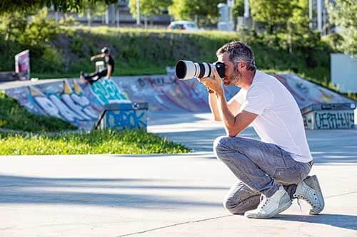Seitenansicht eines Fotografes bei der Arbeit vor einer Skater Anlage