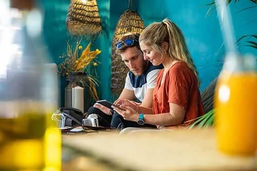 Zwei Touristen sitzen in einer Bar und schauen auf das Smartphone
