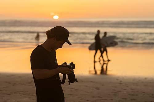 Fotograph schaut am Strand bei Sonnenuntergang auf Canon Kamera Display