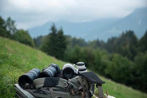 Canon Kameras und Objektive auf einem Rucksack auf einer Wiese am Berghang
